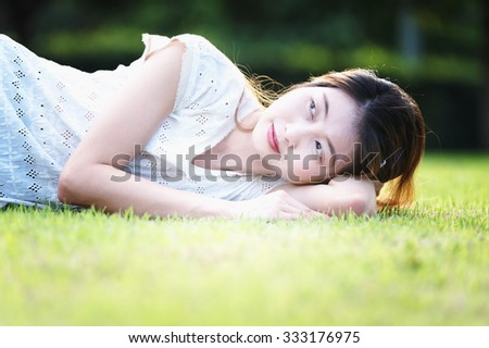 asia beautiful young woman lying on green grass in holiday