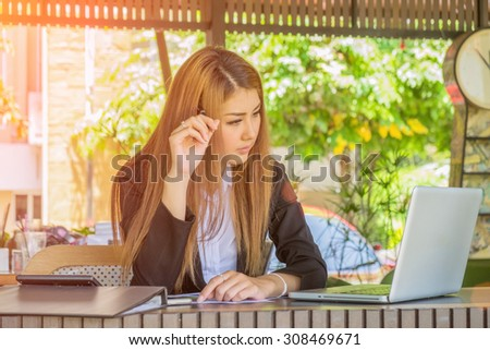 Asia business woman working in a cafe with film filter effect. vintage tone Retro filter effect,soft focus,low light. - stock photo