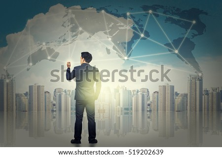 Asia businessman standing on the Bangkok cityscape background and and writing the network line over the world map and sunlight. dicut each elements, Business technology concept