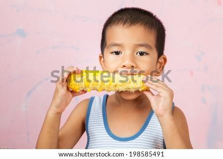 Asia children eats corn with happy mood. - stock photo