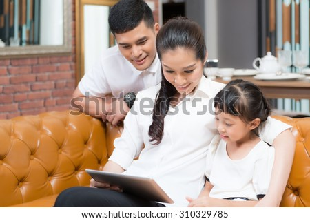 Asia Family Using Laptop Whilst Relaxing On Sofa At Home