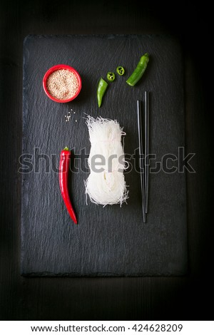 Asia food - rice noodles, spicy pepper, sticks and sesam, ready to cook on a dark stone background, top view - stock photo