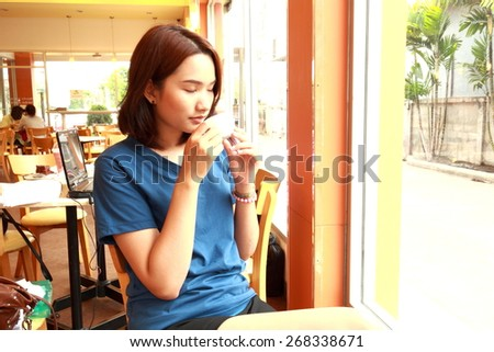 asia girl hold cup of coffee in hand look in window - stock photo