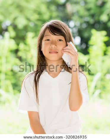 Asia girl use smart phone in garden at summer outdoor - stock photo