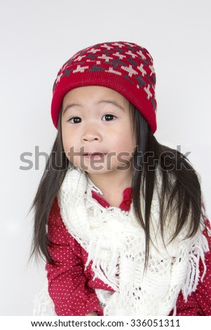 Asia little girl in red cozy sweater and red hat, little girl in christmas    - stock photo