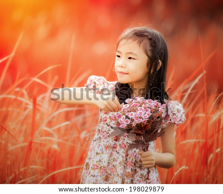 Asia little girl laughing in a meadow - happy girl in autumn background - stock photo