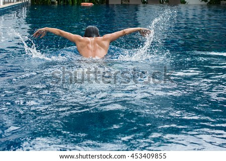 Asia Man doing butterfly strokes while swimming with splash of water pool. View of back Male swimmer performing the butterfly stroke at outdoor swimming pool. Asian Thailand.  - stock photo