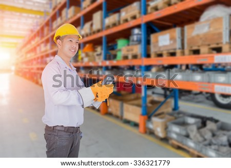 Asia man scanning package with warehouse barcode scanner in modern storehouse - stock photo