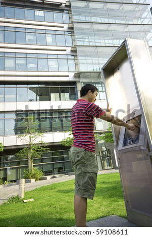 asia man touch the screen at moder building outside - stock photo