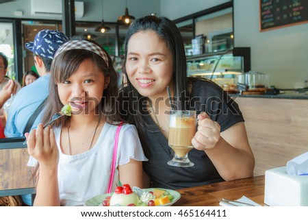 Asia Mother and Daughter eat fruit cheesecake with cherry, kiwi, orange and grape at restaurant.
