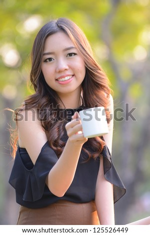 Asia woman drinking coffee in park outdoor. - stock photo