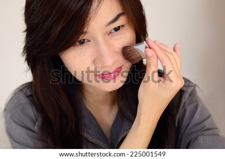 Asia woman makeup your face. Make-up closeup. Cosmetic Powder Brush.