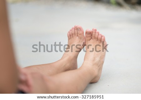 asia woman sitting on  floor. Feet close up. Blurred background.