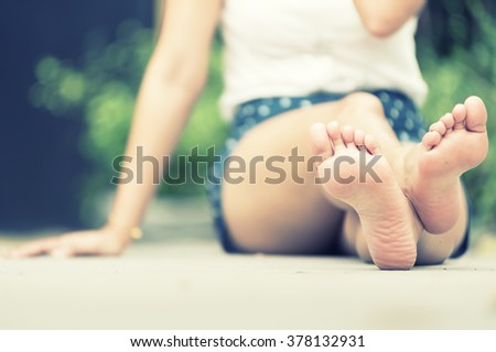 asia woman sitting on  floor. Feet close up. vintage effect - stock photo