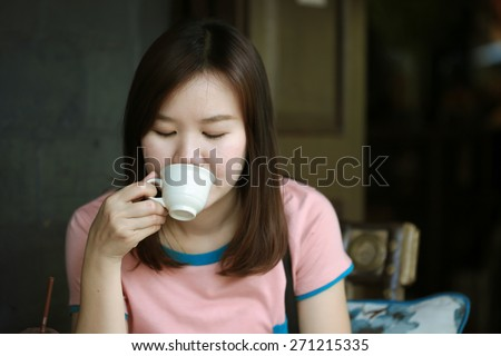 Asia women drinking coffee in cafe shop on free day, Relax time on cafe shop, Beautiful Girl Drinking Tea or Coffee in Cafe - stock photo