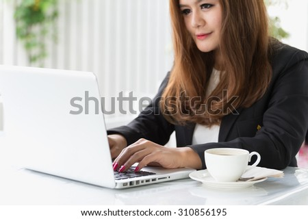 Asia young business woman sitting in a cafe with laptop and coffee, business concept