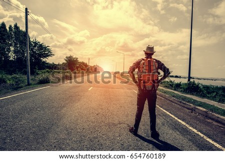 Asia young handsome man traveler with backpack and hat.He standing on the road.Traveling along Asia, active lifestyle concept