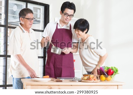 Asian adult son preparing meal for his senior parents at kitchen. Family living lifestyle at home. - stock photo