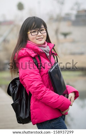 Asian adult student sitting outdoor - stock photo