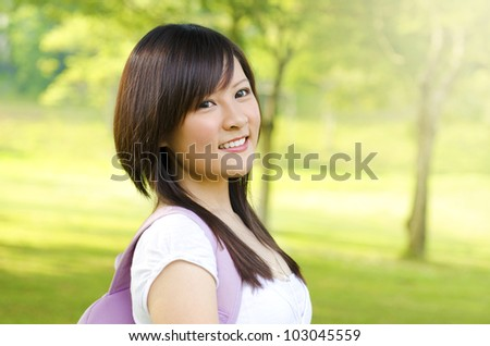Asian adult student standing outdoor park, green tree background - stock photo