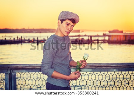 Asian American college student seeking love in New York, wearing newsboy cap, knitting sweater, holding white rose, standing by river in sunset, looking away, thinking. Instagram filtered effect.  - stock photo