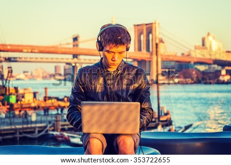 Asian American college student traveling, studying in New York, wearing black leather jacket, headphone, listening music, working on laptop computer. Brooklyn, Manhattan bridges on background.  - stock photo
