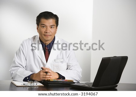 Asian American male doctor sitting at desk with charts and laptop computer looking at viewer. - stock photo