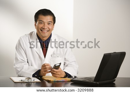 Asian American male doctor sitting at desk with charts and laptop computer using pda. - stock photo