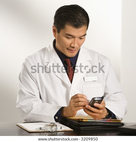 Asian American male doctor sitting at desk with charts using pda. - stock photo