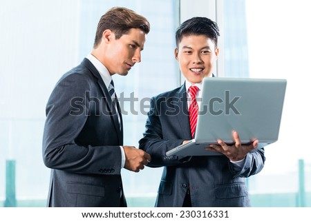 Asian and Caucasian business men discussing project on Laptop - stock photo