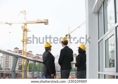 asian architect team in discussion on worksite - stock photo