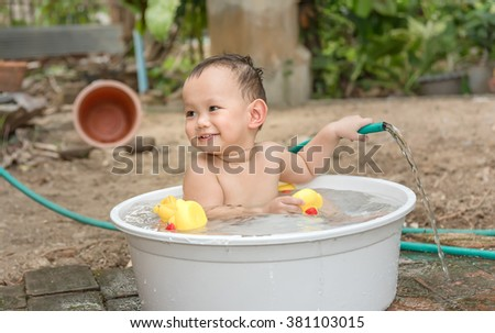 Asian baby boy outdoor bathing in the white bathtub . He is smiling and playing yellow duck full of happiness, Country side culture of Thailand - stock photo