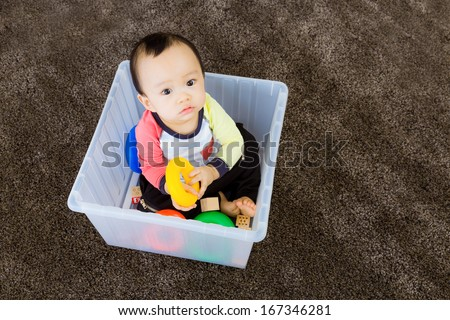 Asian baby boy playing inside the plastic box - stock photo