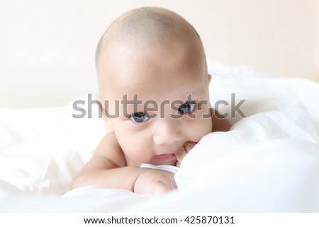 Asian baby boy sucking fingers in bed - stock photo