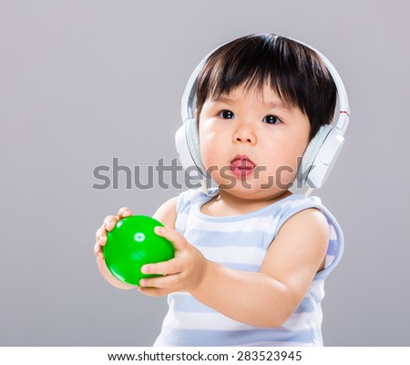 Asian baby boy wear with headphone and play with green ball - stock photo