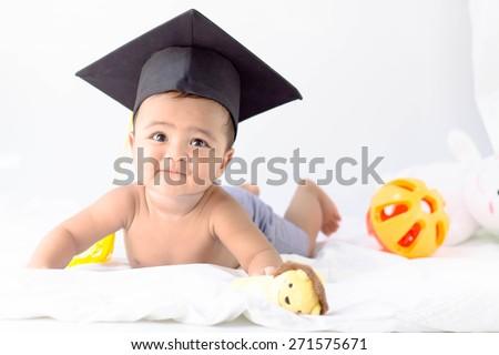 Asian baby boy wearing a graduation black cap - stock photo