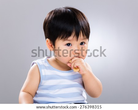 Asian baby boy with finger food - stock photo