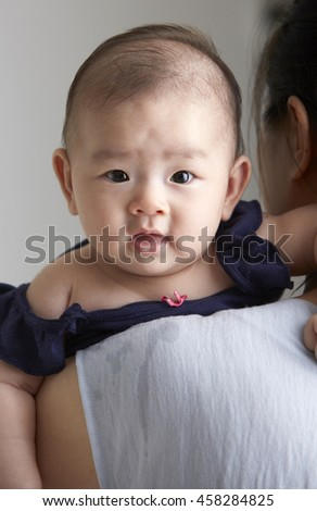 Asian baby closeup, lying on her mother's shoulder