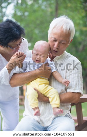 asian baby crying while being comforted by grandparents