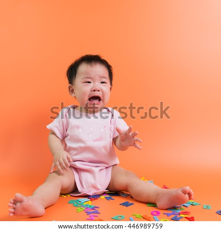 Asian baby crying with wooden alphabets on the floor