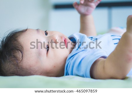 Asian baby cute boy lie supine on the bed