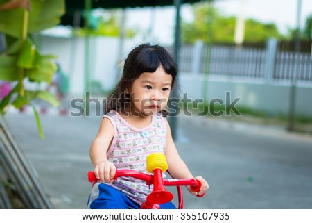 Asian baby cute girl with curly hair are bicycling