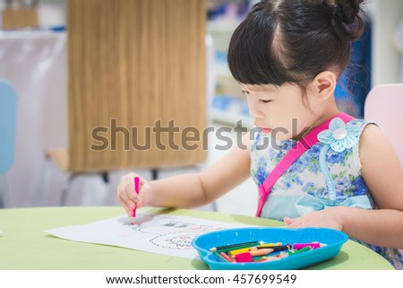 Asian baby cute girl with curly hair paint a cartoon paper