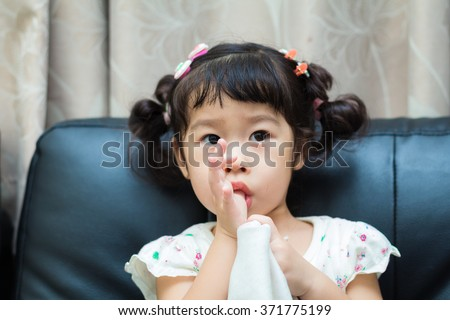 Asian baby cute girl with curly hair suck the finger - stock photo