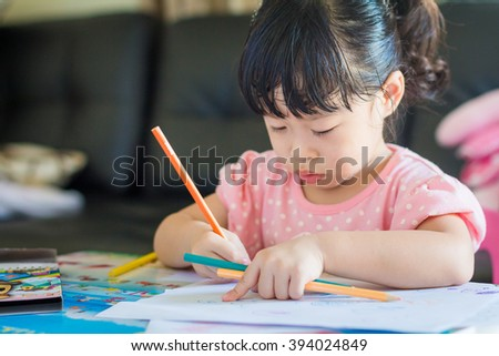 Asian baby cute girl with curly hair write a paper
