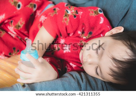 Asian baby drinking milk from bottle while sleeping - stock photo