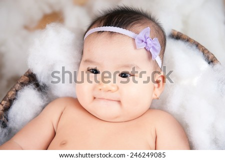 Asian baby face. Feeling dry and happy. Happy little baby smiling while lying in bed - stock photo