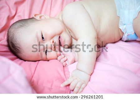 Asian baby girl crying and put her finger in her mouth. she lay on pink bed. - stock photo