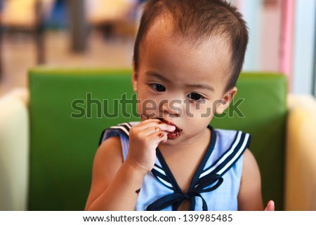 Asian baby girl eating chocolate and mouth is dirty
