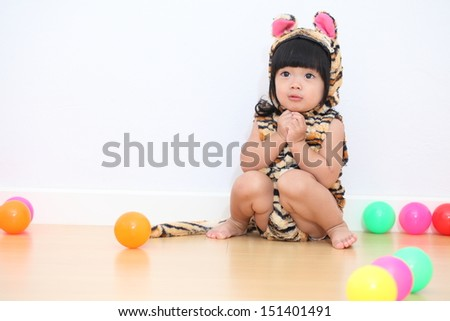 Asian baby girl in tiger suit playing with colorful ball